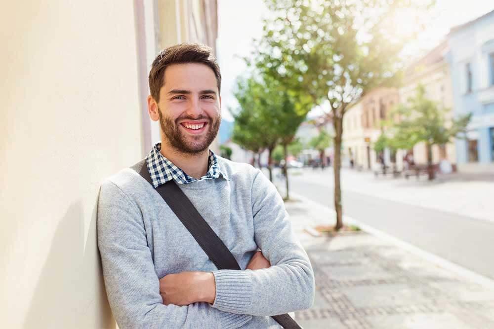 Junger Mann lehnt sich in einer Straße mit Bäumen an eine Hausmauer und lacht in die Kamera.