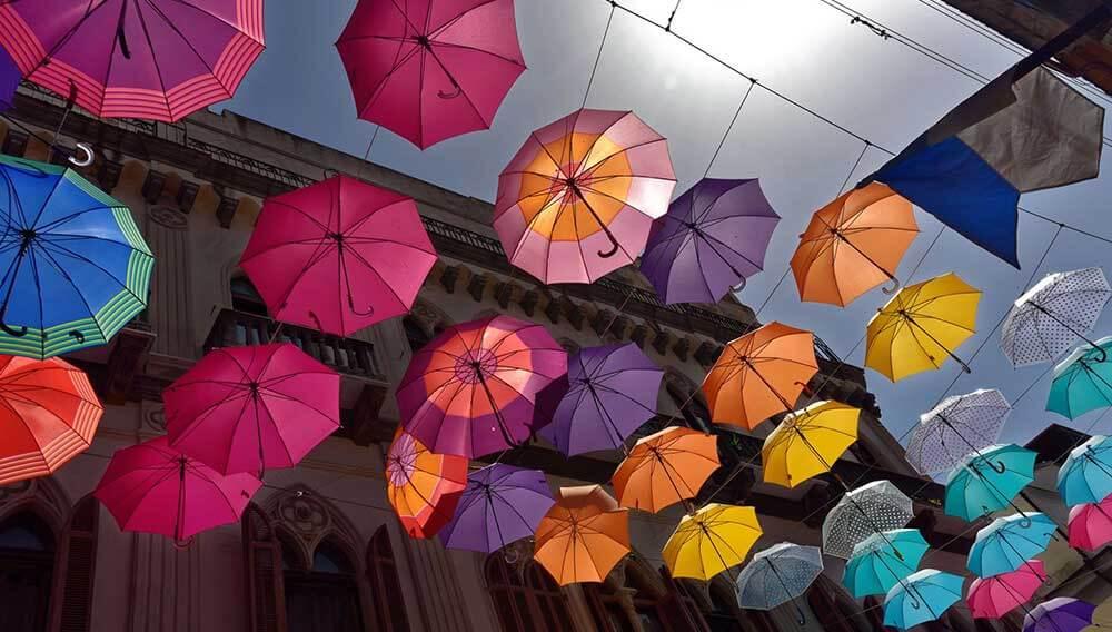 Viele bunte Schirme sind über einer Strasse zwischen Häusern aufgehängt. Die Sonne scheint und zwischen den Schirmen ist der Himmel zu sehen.