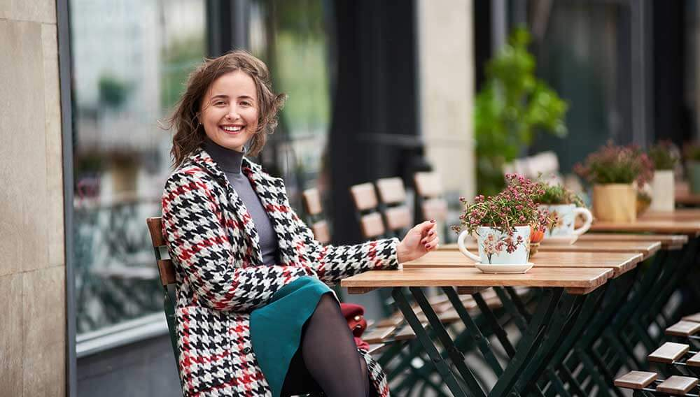 Eine Frau sitzt bei Wind in einem Gastgarten vor einem Lokal. Foto um den Geschäftsbereich Windkomfort der Firma Weatherpark zu illustrieren.