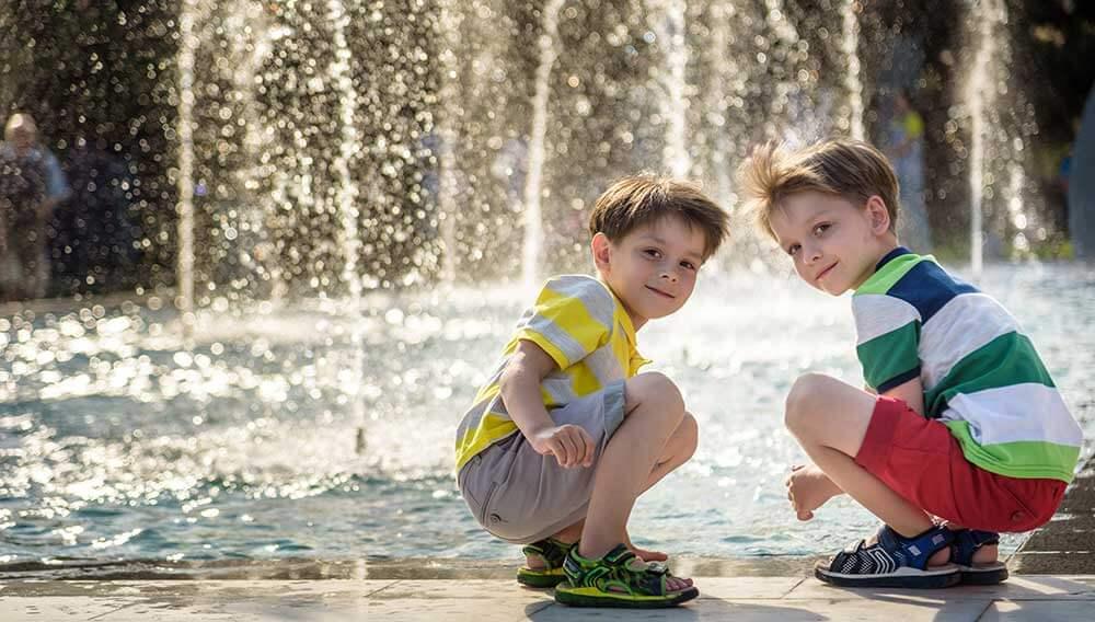 Zwei Buben spielen vor einem großen Springbrunnen. Illustration für den Geschäftsbereich Sommerkomfort der Firma Weatherpark.