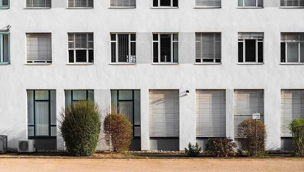 Ein weißes moderenes Haus mit Jalousien, um den Geschäftsbereich